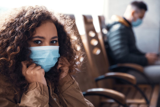 African-American woman with disposable mask indoors. Virus protection