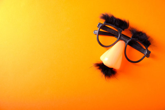 Overhead glasses, nose and mustache for April 1, April Fool's Day, on orange background