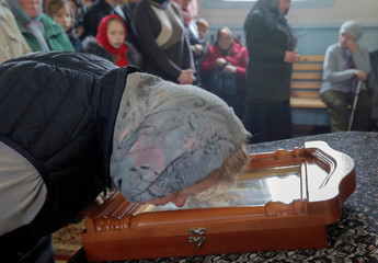 Woman kisses an icon during a service in an Orthodox Church in Dyatlovo