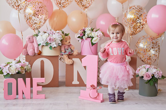 Smash cake party. Little cheerful birthday girl with first cake. Happy infant baby celebrating his first birthday. Decoration and photo zone for first year. One year baby celebration. Pink decor.