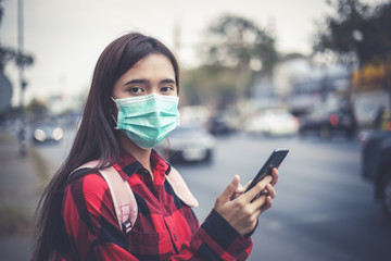 Asian Young woman using smart phone in the city wearing face mask because of air pollution, particulates and for protection flu virus, influenza, coronavirus
