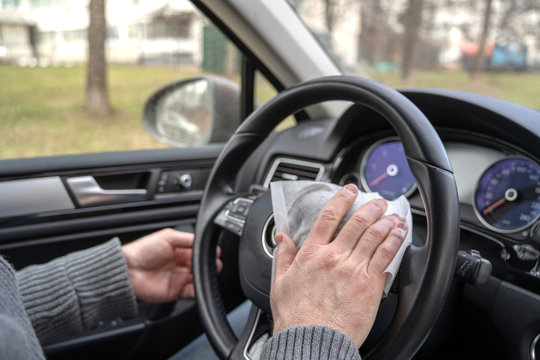 Man cleaning steering wheel of a car using antivirus antibacterial wet wipe (napkin) for protect himself from bacteria and virus.