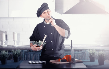 Man cook preparing food at the kitchen of vegetables