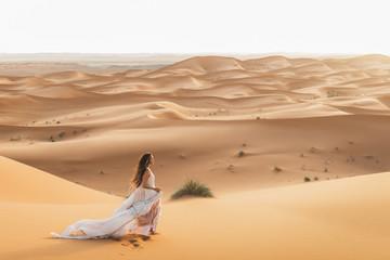 Portrait of bride woman in amazing wedding dress in Sahara desert, Morocco. Warm evening light, beautiful pastel tone, sand dunes on horizon. Nature background. Fotomurales