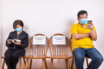 People with face mask seated in-between two chairs at public place with Social Distancing, Do Not...