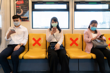 Three Asian people wearing mask sitting in subway distance for one seat from other people keep...