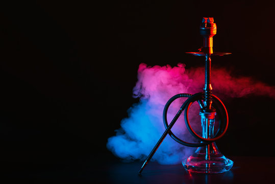 hookah with a glass flask and a metal bowl shisha with colored smoke on the table