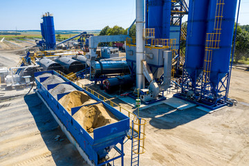 Equipment for production of asphalt, cement and concrete. Concrete plant. High tower of an asphalt plant. Harmful production. A mixture of bitumen and gravel, a mix machine. Aerial view. Fotomurales