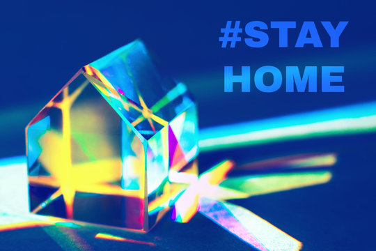 Closeup of colorful glass prism house on trendy blue background with rainbow light refraction and shadows with text STAY HOME. Concept of prevention the coronavirus from spreading.