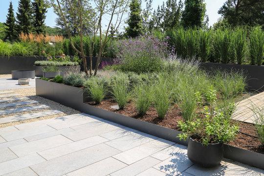Moderne Garten- und Terrassengestaltung im Materialmix:Terrassen aus Holz, Steinplatten und Schotter sowie Metall Pflanzgefäße mit Gräsern, Bäumen und blühenden Kübel Pflanzen