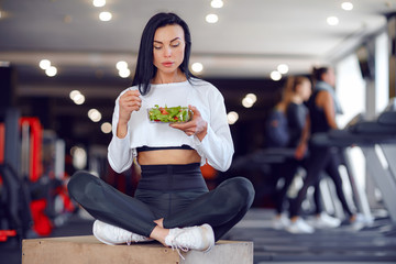 Beautiful sport woman in sportswear eating salad in gym.