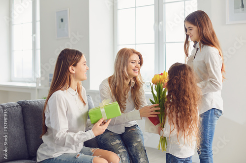 Happy Mother's Day. Children daughters give mom a bouquet of flowers at home.