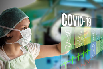 Coronavirus Covid-19 concept image with doctor woman using futuristic touch monitor interface with text and icons with surgery operating room on background looking for vaccine with mask on her face