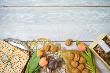 Jewish holiday Passover celebration concept with seder plate, matzah and tulip flowers on wooden table. Pesah background. Top view from above.