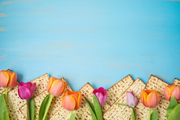 Jewish holiday Passover celebration concept with matzah and tulip flowers on wooden table. Pesah...