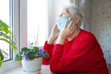 The Covid-19, health, safety and pandemic concept - senior old lonely woman sitting near the window Wall mural
