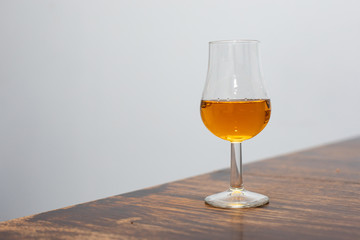 Poster Alcohol close-up of whiskey tasting glass with whiskey held in a hand on a gray background