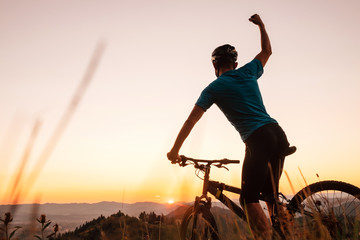 Man biker man meets a sunset in top of hill. He rising a one arm greeting on another successful day...