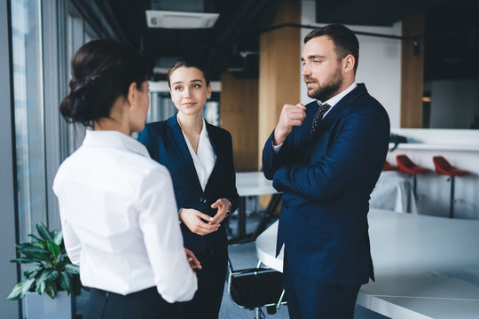 Attentive colleagues having conversation while standing in office lobby