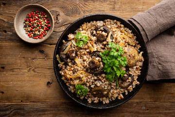 Buckwheat porridge with mushrooms in the frying pan on wooden table, top view Wall mural