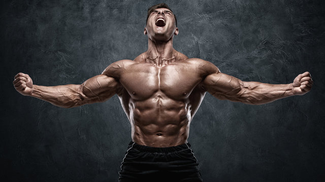 Muscular man showing muscles on wall background. Strong male naked torso abs