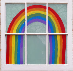 Painted rainbow framed inside home's window.