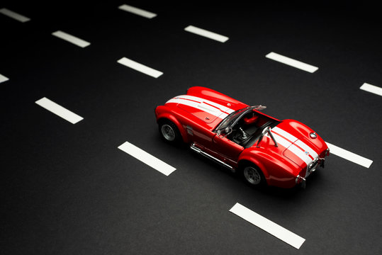 Top and rear view of a Red Ford Shelby 427 Cobra Toy car on aasphalt road with road lanes.