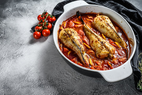 Monkfish baked in tomatoes in a baking dish. Black background. Top view. Copy space