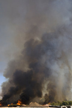 Brush fire in desert emitting large black plumes of smoke, east of Needles in Arizona