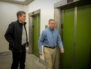 Sen. Steve Daines (R-MT) and Sen. Lindsey Graham (R-SC) head to an elevator after a luncheon meeting to wrap up work on coronavirus economic aid legislation