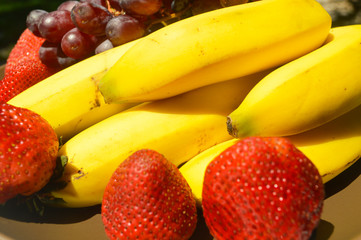 Tropical fruits as banana mango strawberries black grapes  in a brown plate garden picture image background