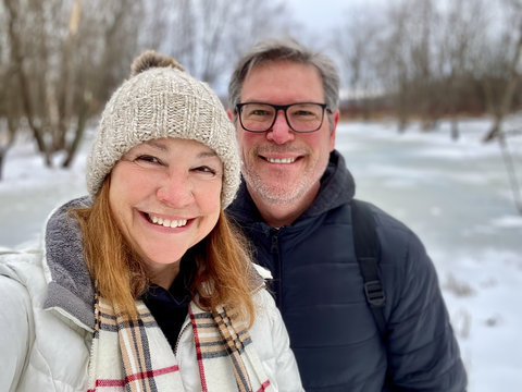 Happy middle aged couple taking a selfie outdoors in winter