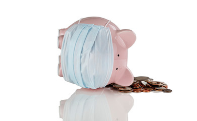 Tipped over piggy bank with medical mask on and coins for financial crisis concept
