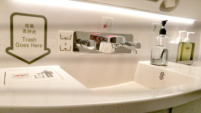 Bathroom sink in a commercial airplane with personal cleaning products