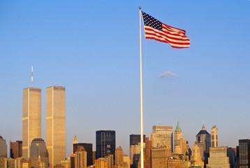 Fototapete - American Flag flying over skyline of New York City from New York Harbor, NY