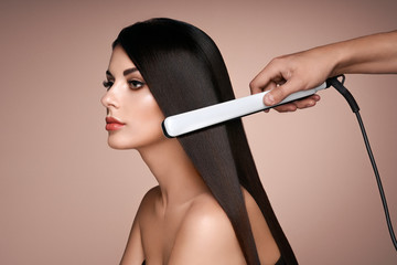 Spoed Fotobehang Kapsalon Hairdresser straightening long dark hair with hair irons. Beautiful woman with long straight hair. Smooth hairstyle