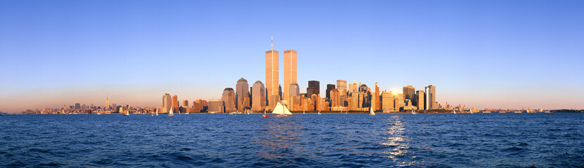 Fotomurales - Panoramic view of sailboat on the Hudson River, lower Manhattan and New York City skyline, NY with World Trade Towers at sunset