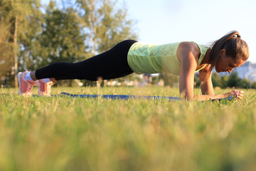 Athletic woman doing plank exercise outdoor. Work out concept.