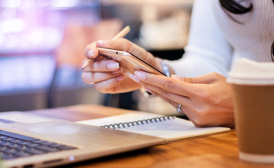 Close-up of hand business woman using mobile phone to searching information from internet while she working with laptop on desk