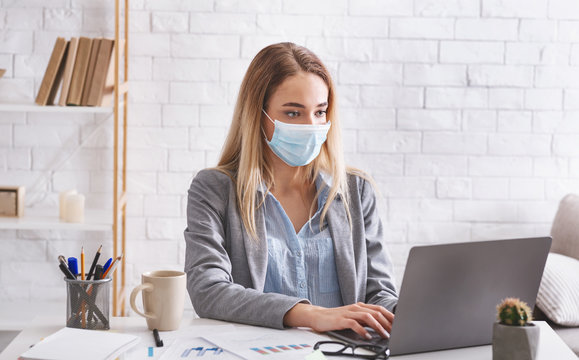 Remote work during epidemic. Woman works in protective mask