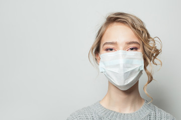 Young woman wearing a face mask on gray background. Flu epidemic and virus protection concept