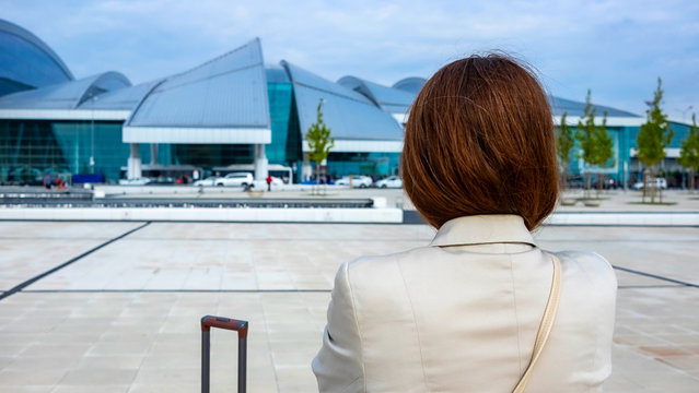 Rostov-on-Don,Russia - April 29,2018: rear view Girl. looks at the airport before traveling, getting ready to board the plane. next to it is the handle of the suitcase. her baggage