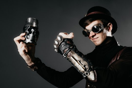 Steampunk actor in glasses and hat posing.