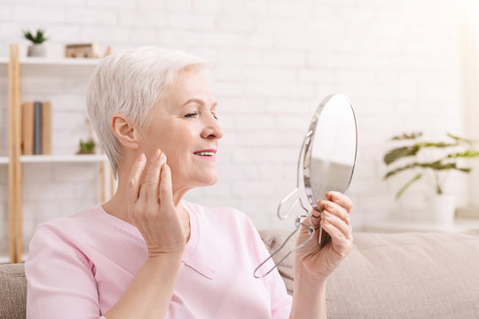 Senior lady massaging her face with mirror at home