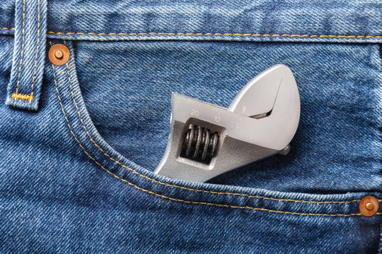 Blue jeans front pocket with adjustable spanner. Close up view. Libor day concept