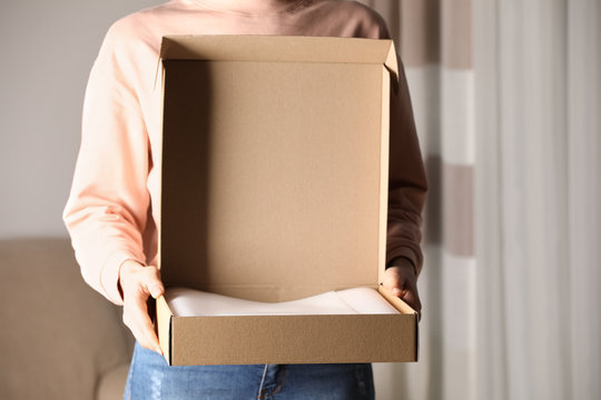 Woman with open cardboard box at home, closeup