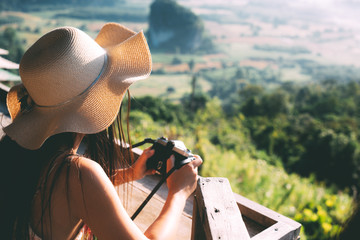 Summer beautiful girl holding a mountain view camera
