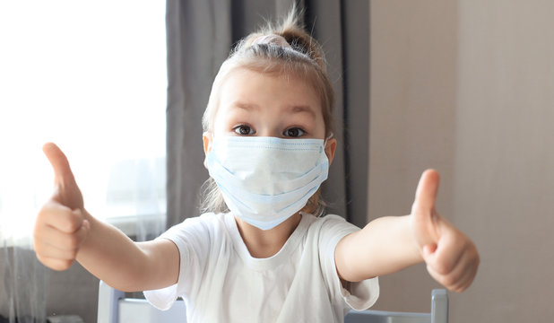 Little girl in a medical mask showing thumb's up gesture. Protection against coronavirus.