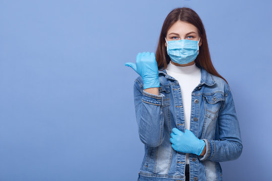 Image of brunette Caucasian woman with long hair, wearing medical face mask and disposable gloves pointing thumb aside at copyspace, isolated over blue background. Coronavirus, covid 19 concept.