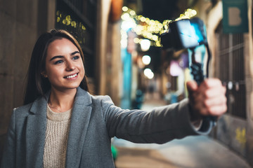Fotomurales - Tourist female blogger shooting video for social media with digital camera. Smiling  woman taking selfie videovlog on light night europe city